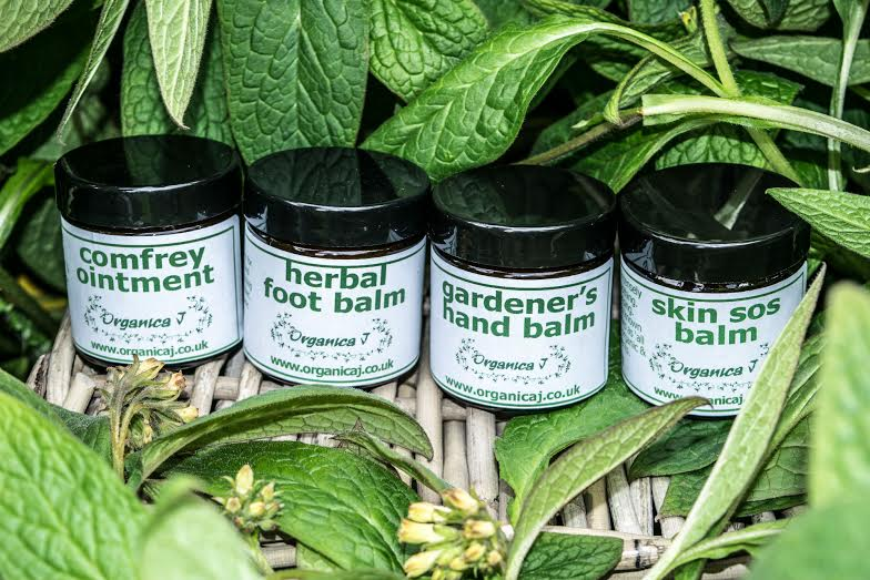 jars of comfrey ointment, herbal foot balm, gardener's hand balm and  and skin SOS balm